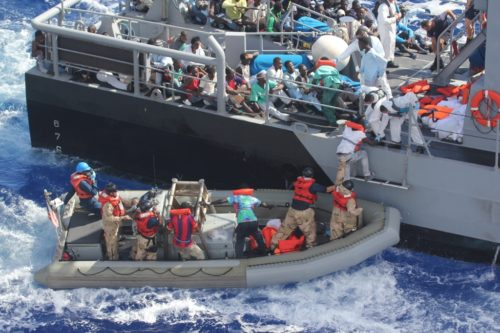 Distressed persons are transferred to a Maltese patrol vessel.
