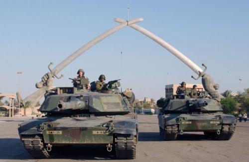 """Tanks M1A1 Abrams de l'US Army devant le monument """"Hands of Victory"""" en novembre 2003 à Bagdad."""