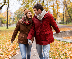 love, relationships, season and people concept - happy young couple walking in autumn park and talking